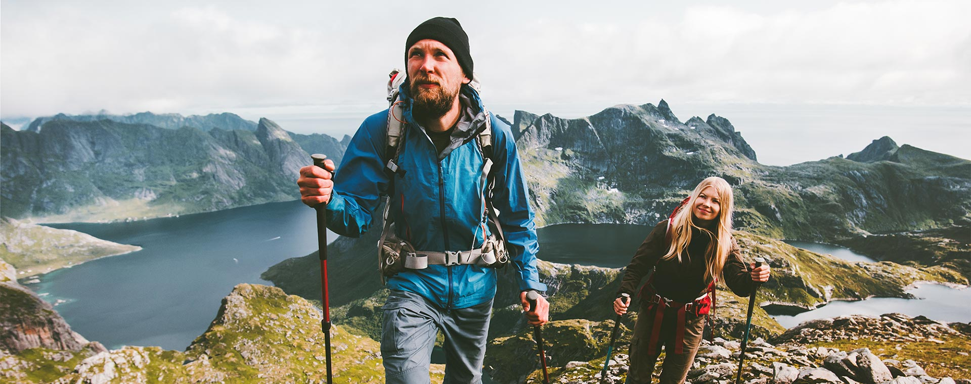 A man and a woman are hiking in the mountains, they have reached a summit and behind them is a lake. They are both wearing rain coats and large backpacks. They are using poles to assist in walk.
