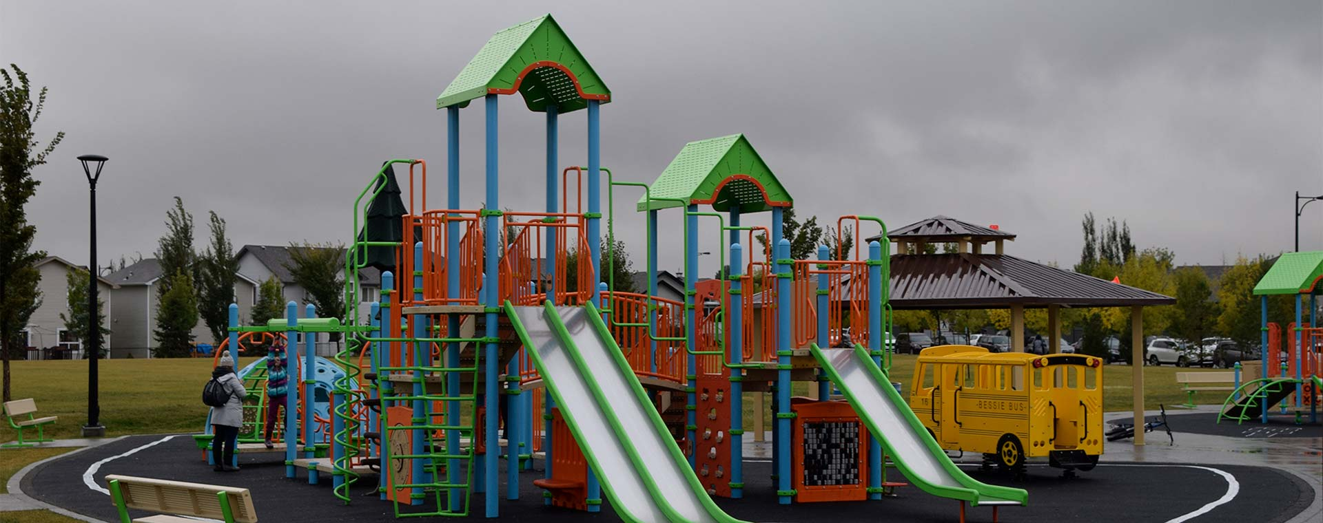 A large playground, with two slides in West Edmonton. The playground is red, blue, green and yellow. There is a gazebo just behind the playground