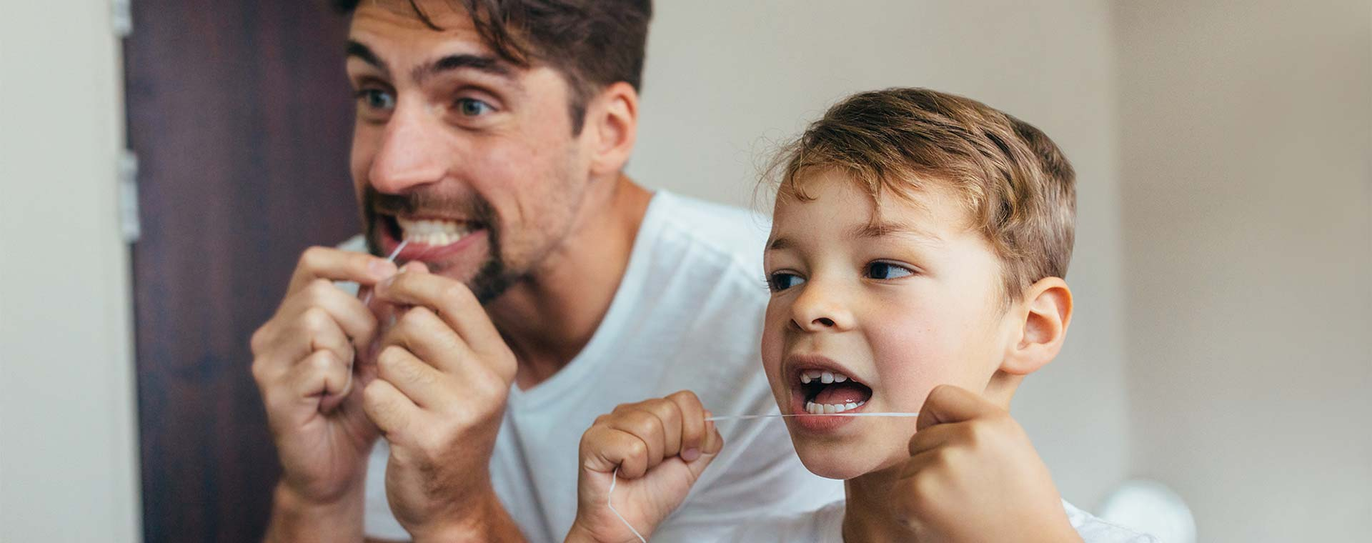 A father and son stand in front of a mirror and are flossing their teeth.