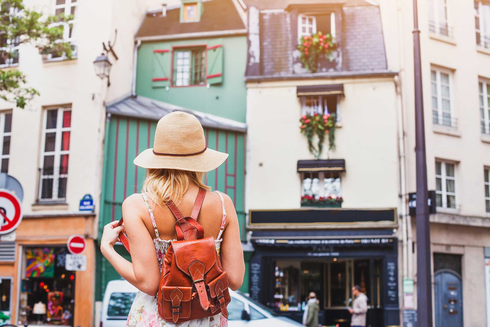 A photo taken from behind a young woman in a European city. She has a wide brimmed, straw hat and is wearing a summer dress, with a small, brown leather backpack.