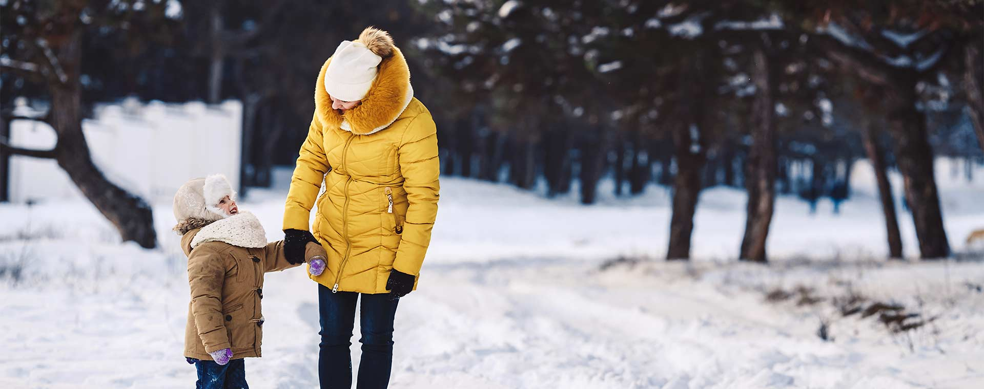 A mother in a yellow, puffy winter coat and her daughter in a light brown, puffy winter coat are walking in a forest. There is snow on the ground and in the trees.