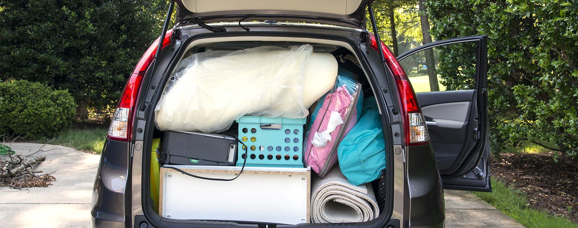 A view of the trunk of an SUV that is fully packed with boxes, blankets, suitcases