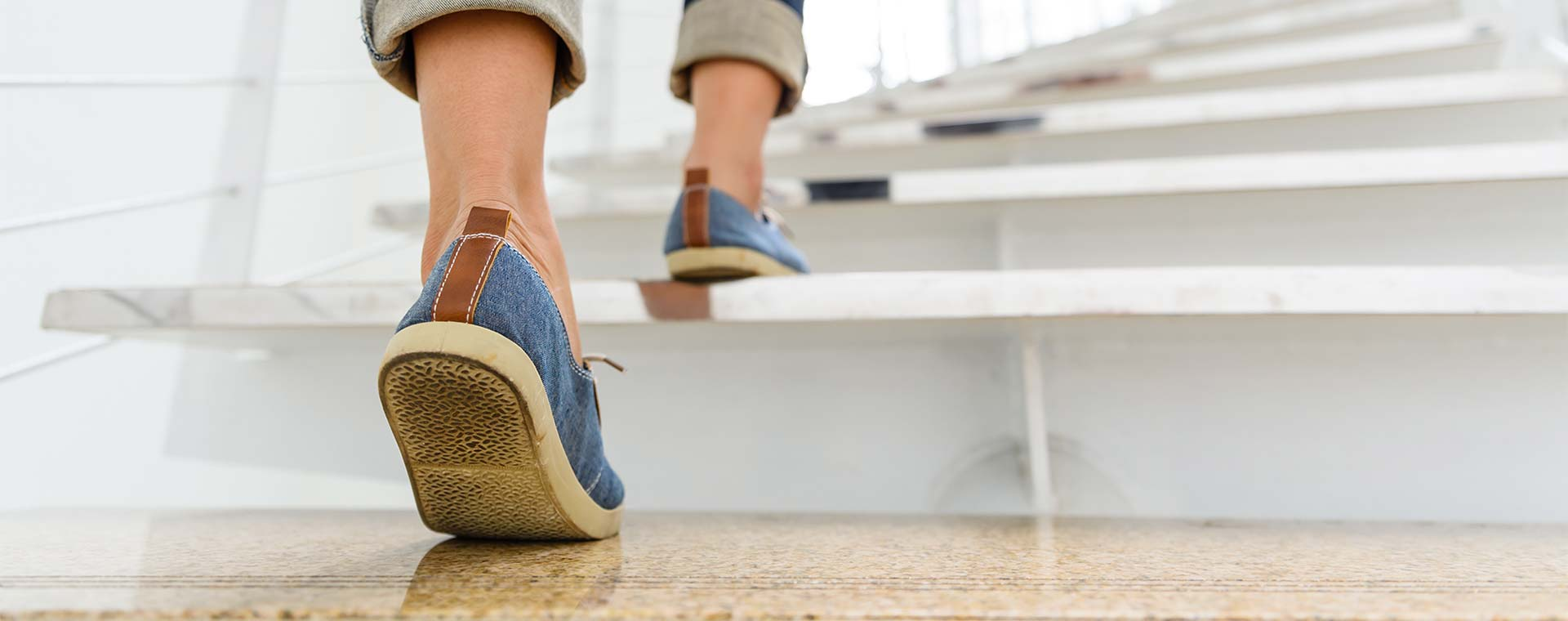 Close up of a young woman walking up stairs in flat, denim colored shoes.