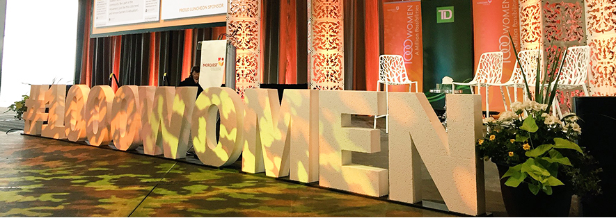 A side-on shot of a stage set to host a panel. There are black and red curtains handing behind the stage, with decorative screen just in front of the curtains. There are four white chairs, that have a back to match the screens, on the stage. In front of the stage in large, block Styrofoam letters it says Hashtag One Thousand Women.