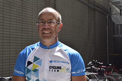 Barry in a Team Alberta Blue Cross cycling shirt, standing in front of a bicycle rack.