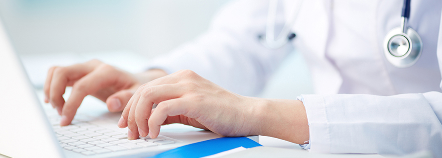 A close up of a doctor using a laptop. There is a stethoscope hanging around their neck. You cannot see their face.