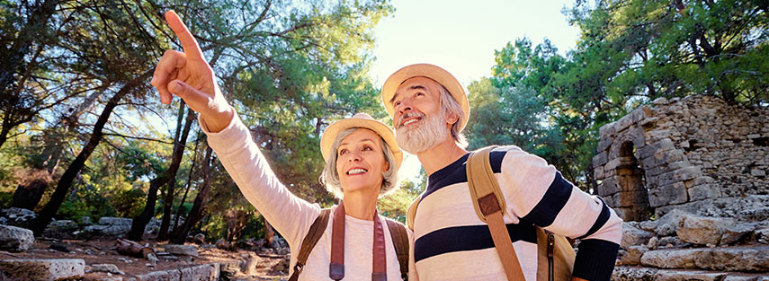 A couple in their early sixties are standing in front of ruins. There are many trees surrounding the ruins and the sun is just behind the couple. They are both wearing hats and backpacks, the woman has a camera around her neck.