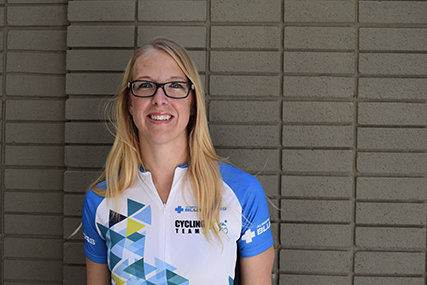 Janelle standing in front of a brick wall in a Team Alberta Blue Cross cycling shirt