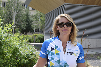 Rebecca is in a Team Alberta Blue Cross cycling shirt, standing in front of trees on the Legislative grounds in Edmonton, AB.