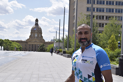Sandeep in a Team Alberta Blue Cross cycling shirt standing near a fountain, with the Alberta Legislative Building in the background.