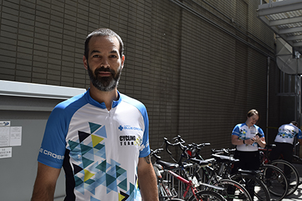 Sean standing in front of a bike rack wearing a Team Alberta Blue Cross cycling shirt