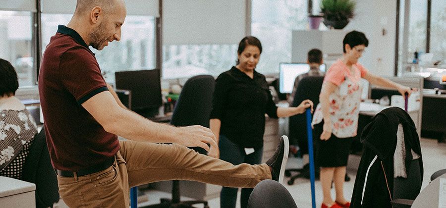 A multiracial group of business people in an open concept office, using items commonly found in the workplace to assist in stretching. In the background are two people sitting at their computers.
