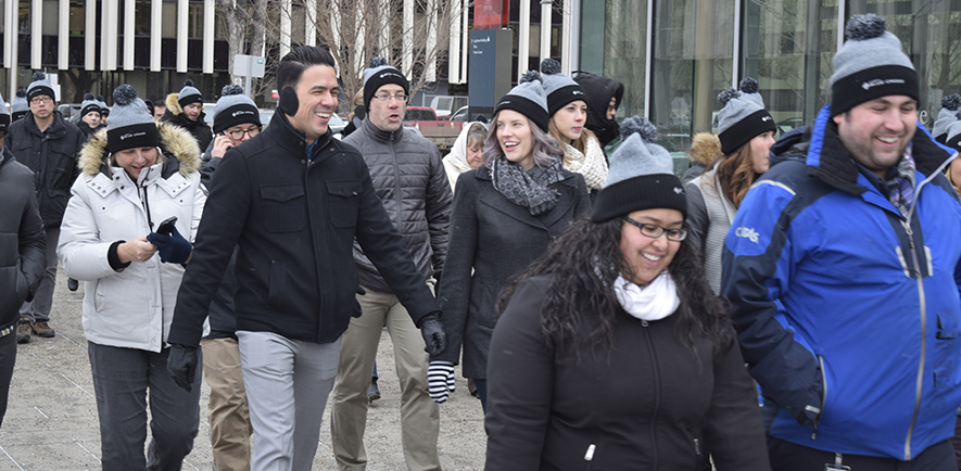 A large, multiracial group of Alberta Blue Cross employees in winter coats, mitts and toques are walking in downtown Edmonton, AB.