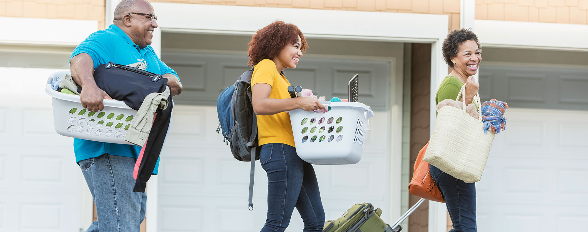 A young, African American woman is moving with the help of her parents. She is in the middle, carrying a white laundry basket that is full of household items. Her father is behind her and also carries a white laundry basket full of clothes. Her mother is in the front, carrying two full bags and toting a suitcase behind her.