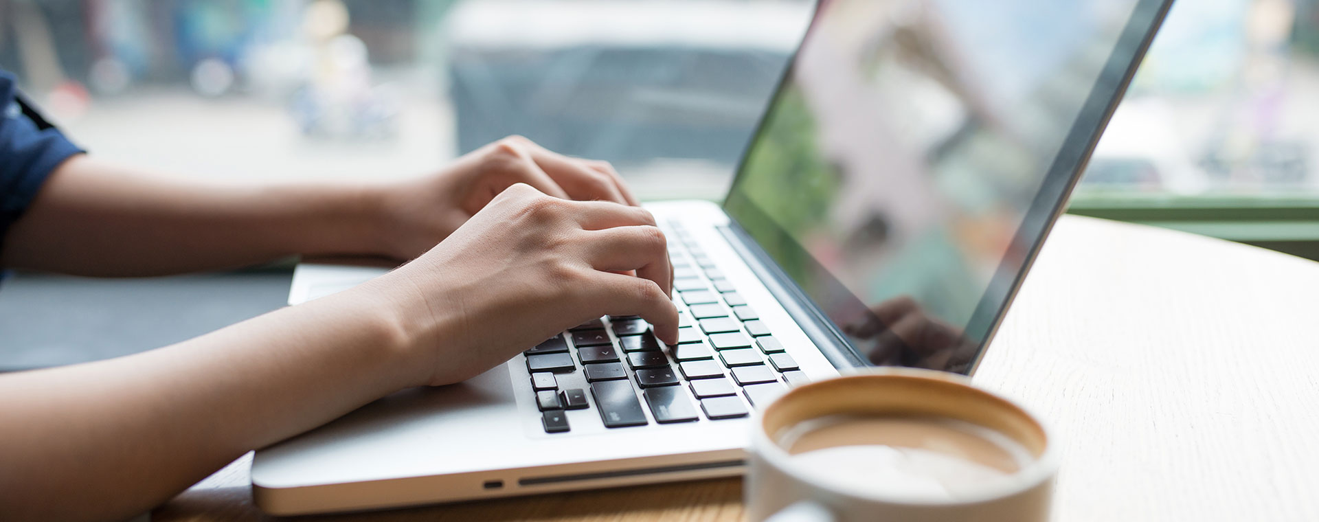 A woman is typing on a laptop, only her forearms are visible. She is sitting at a light, wooden table with a cup of coffee beside the laptop.