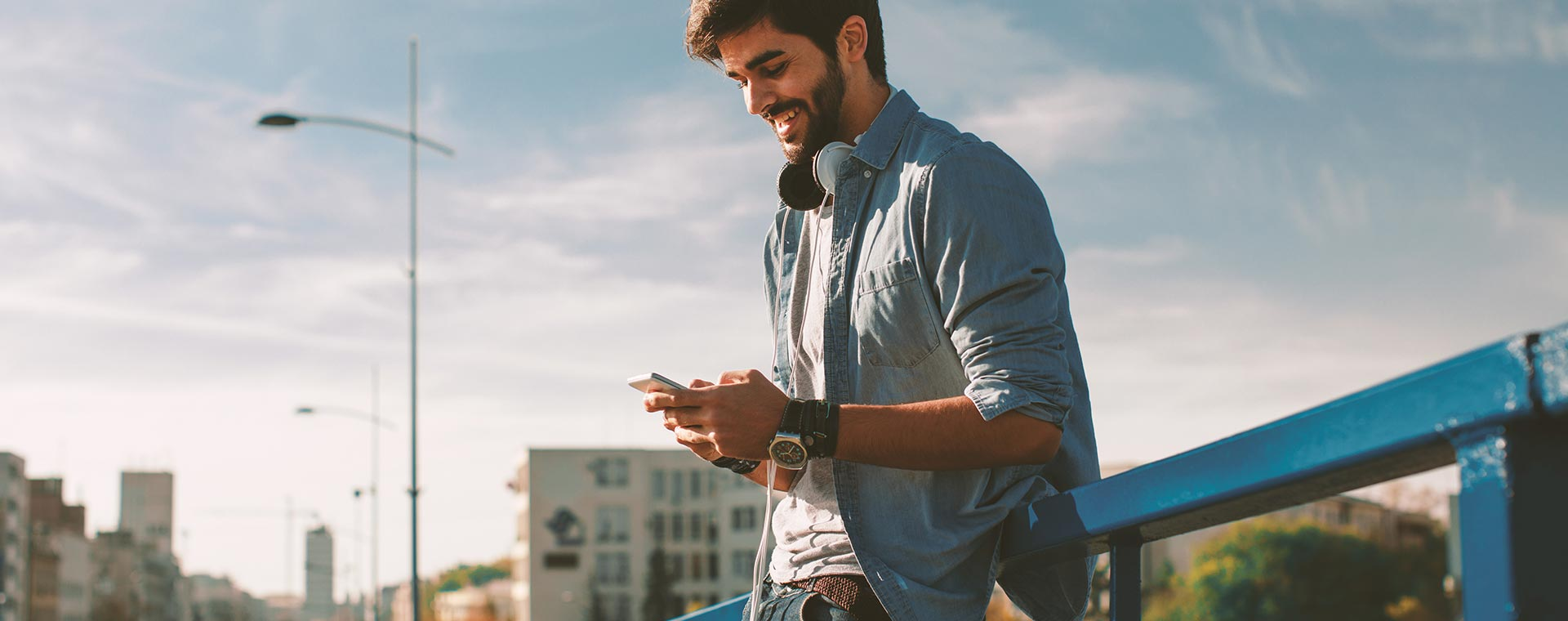 A young man leans against a bridge rail, with a cityscape in the background, while his is looking down at his smartphone, smiling.