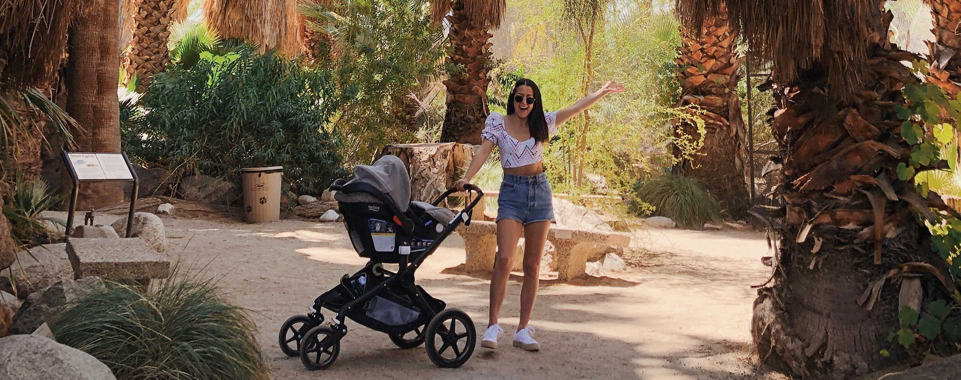Lindsay Smith standing amid tropical trees, with a stroller beside her.
