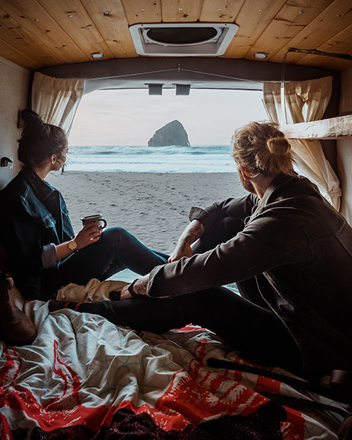 Jay R. Mcdonald and a women sit in the back of a van, drinking coffee and looking out over a beach that leads to the ocean.