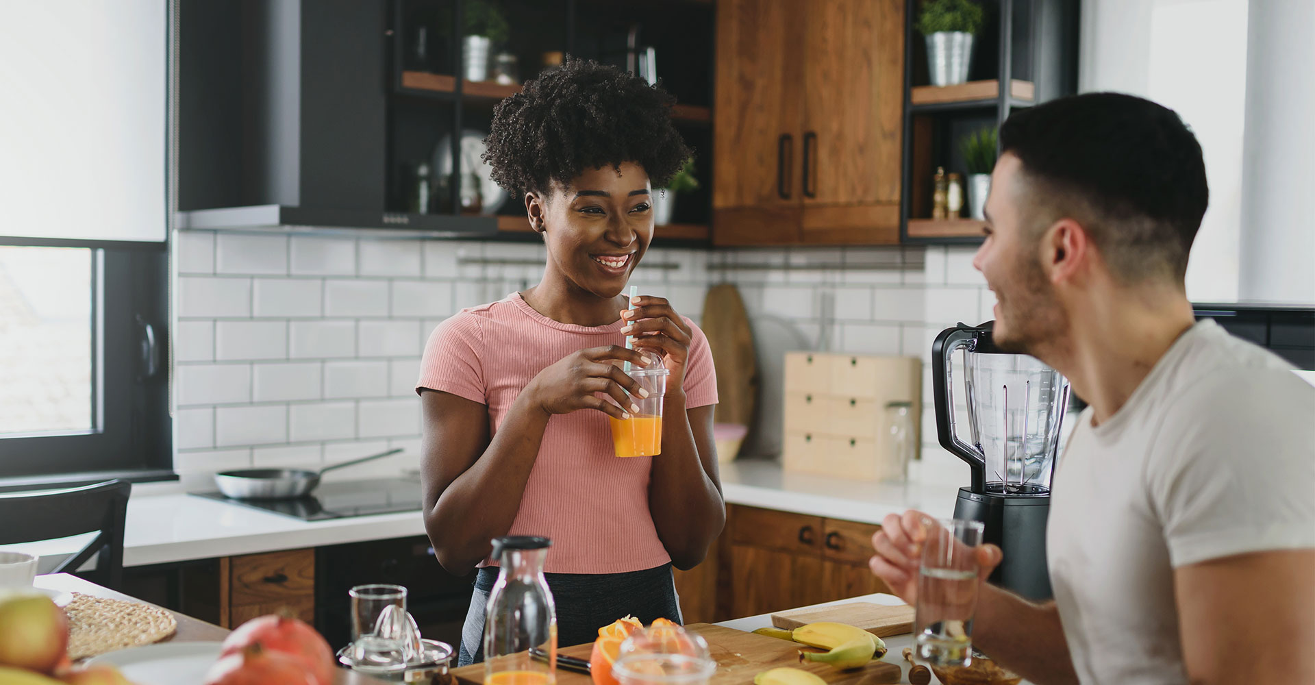 A young, happy, multiracial couple are have eating breakfast in a modern-farmhouse style kitchen. They have lots of fruit on the counter and are drinking fresh orange juice.