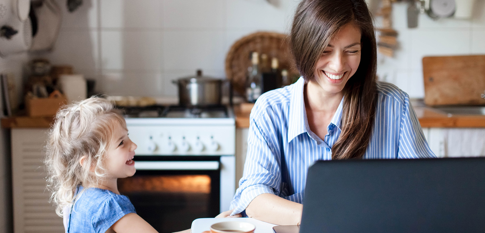 Working mom works from home office. Happy mother and daughter smiling. Successful woman and cute child using laptop. Freelancer workplace in cozy kitchen. Female business. Lifestyle authentic moment.
