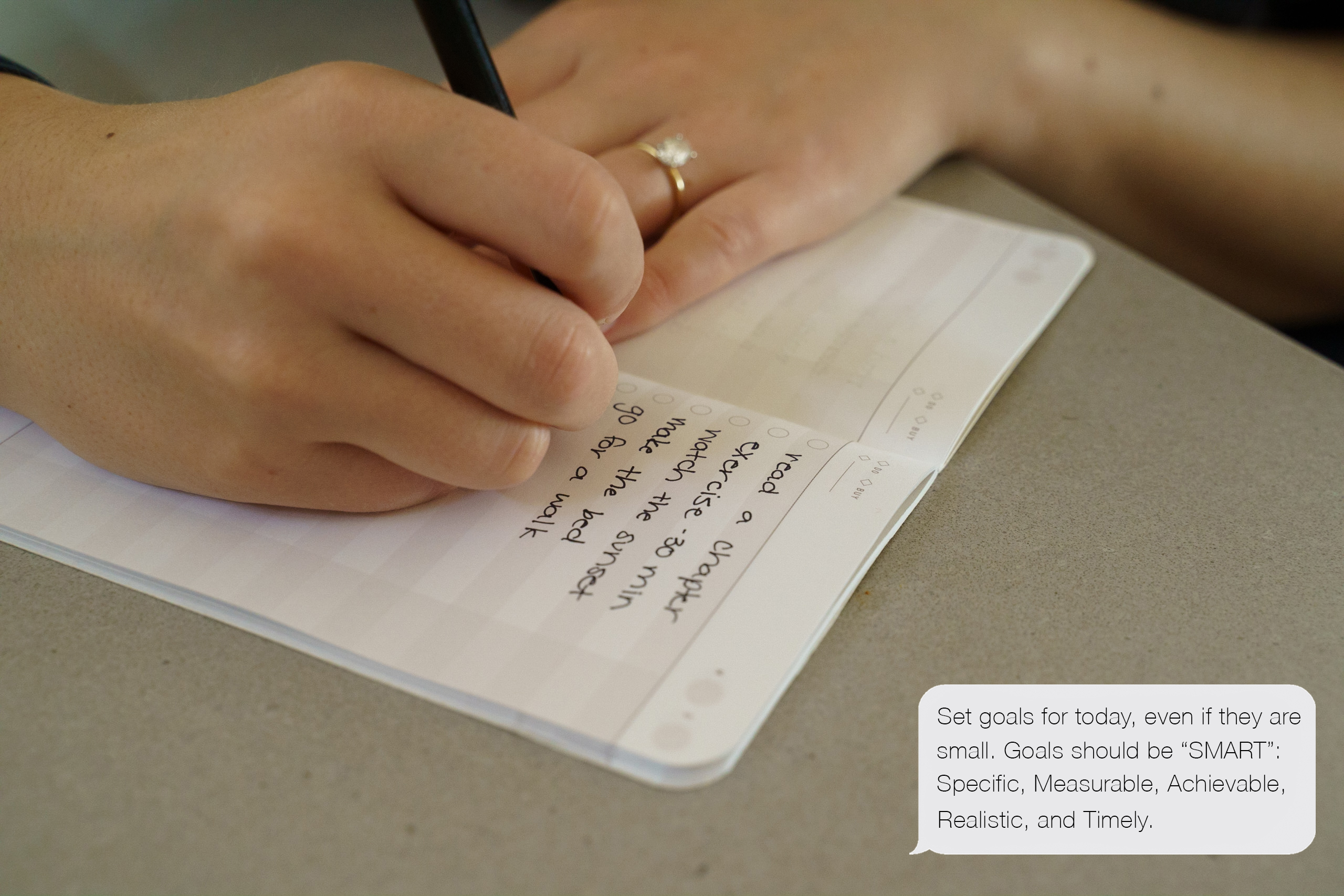 Person writing daily goals in journal.