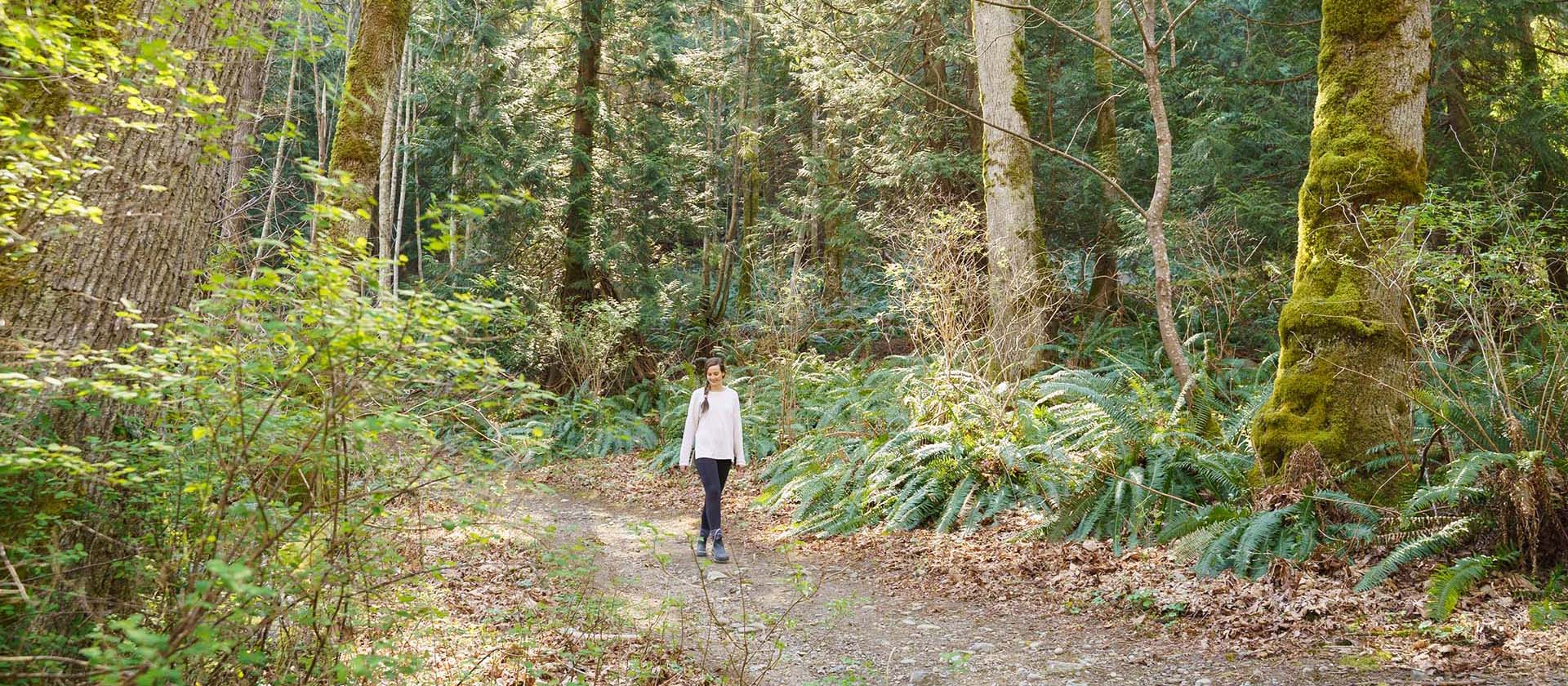 Woman walking along forest path