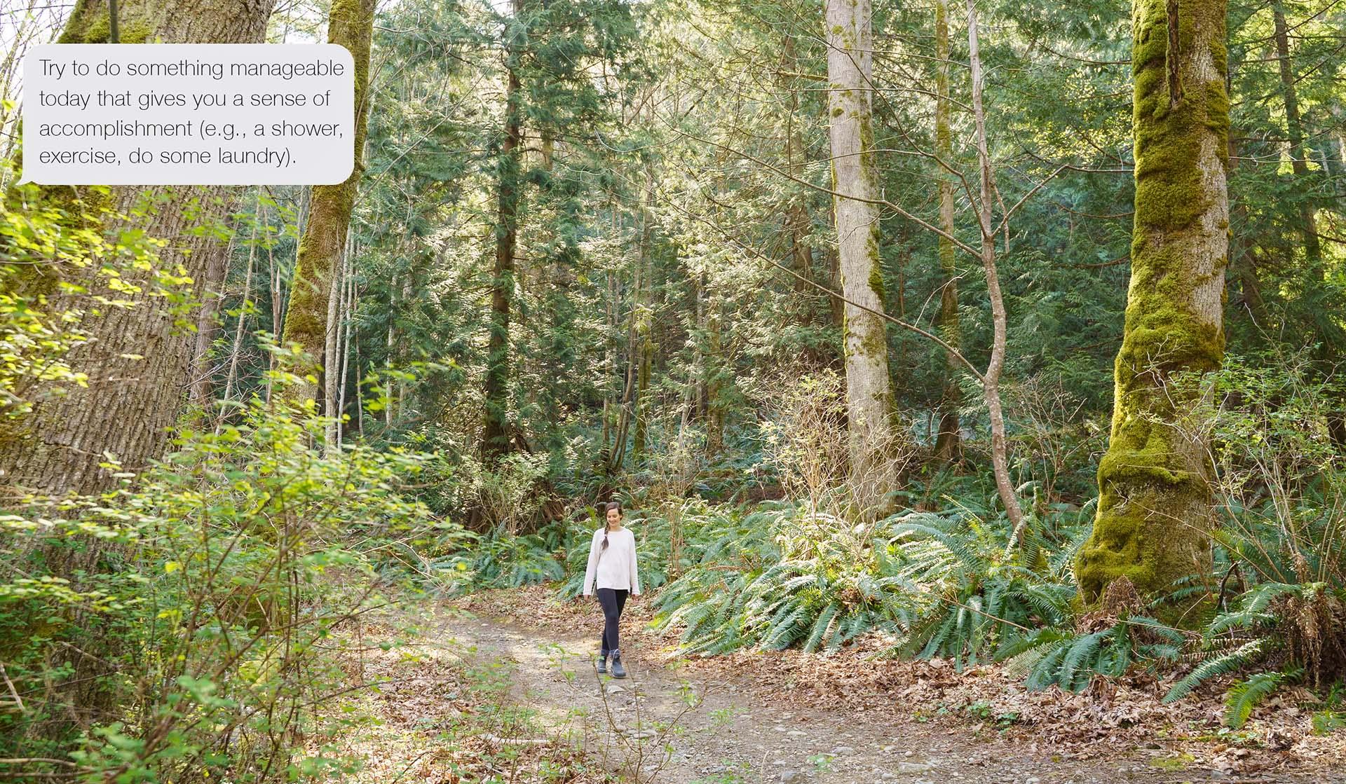 Woman walking along forest path.