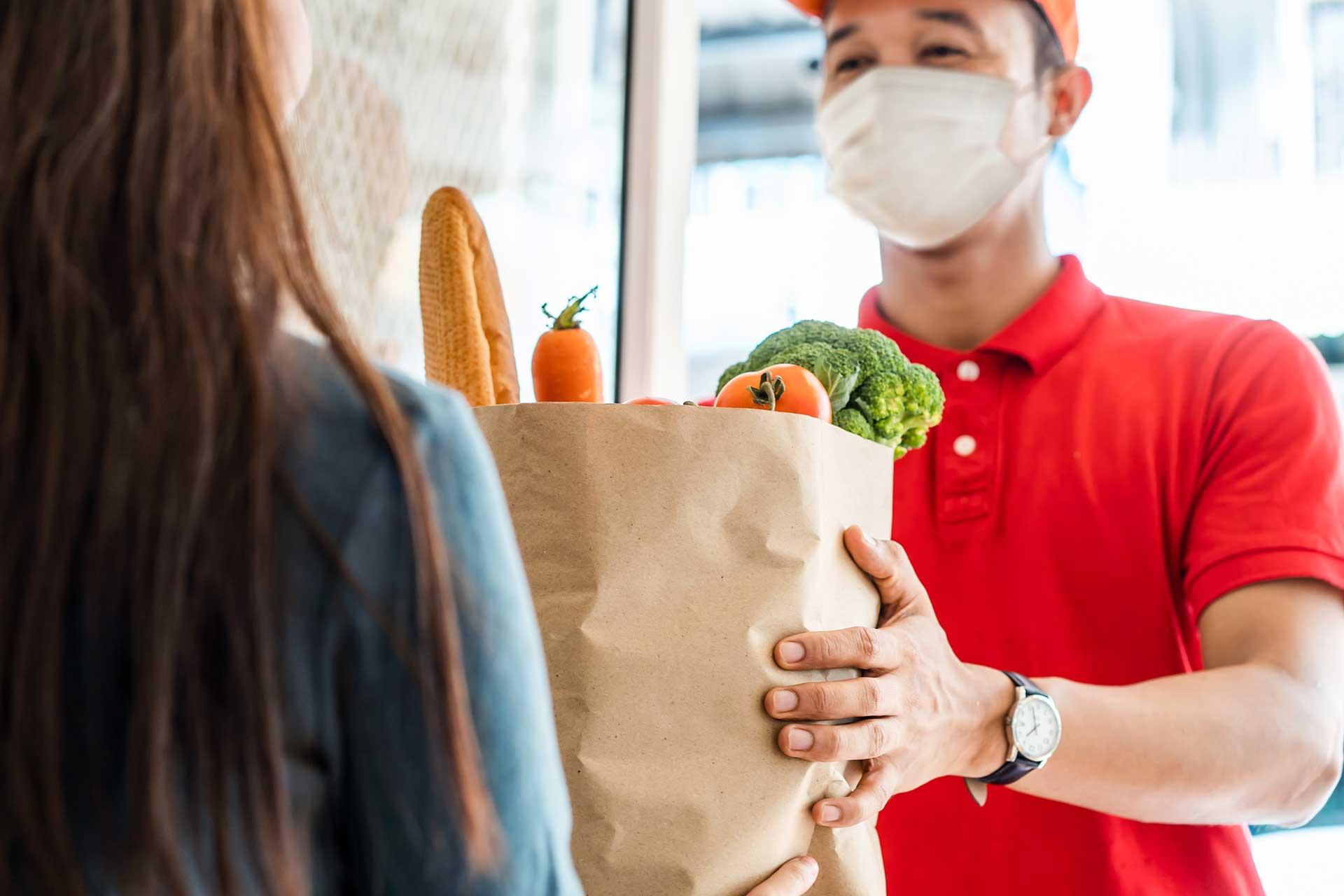 Delivery man wearing face mask in red uniform handling bag of food, fruits, vegetables to female costumer in front of the house.