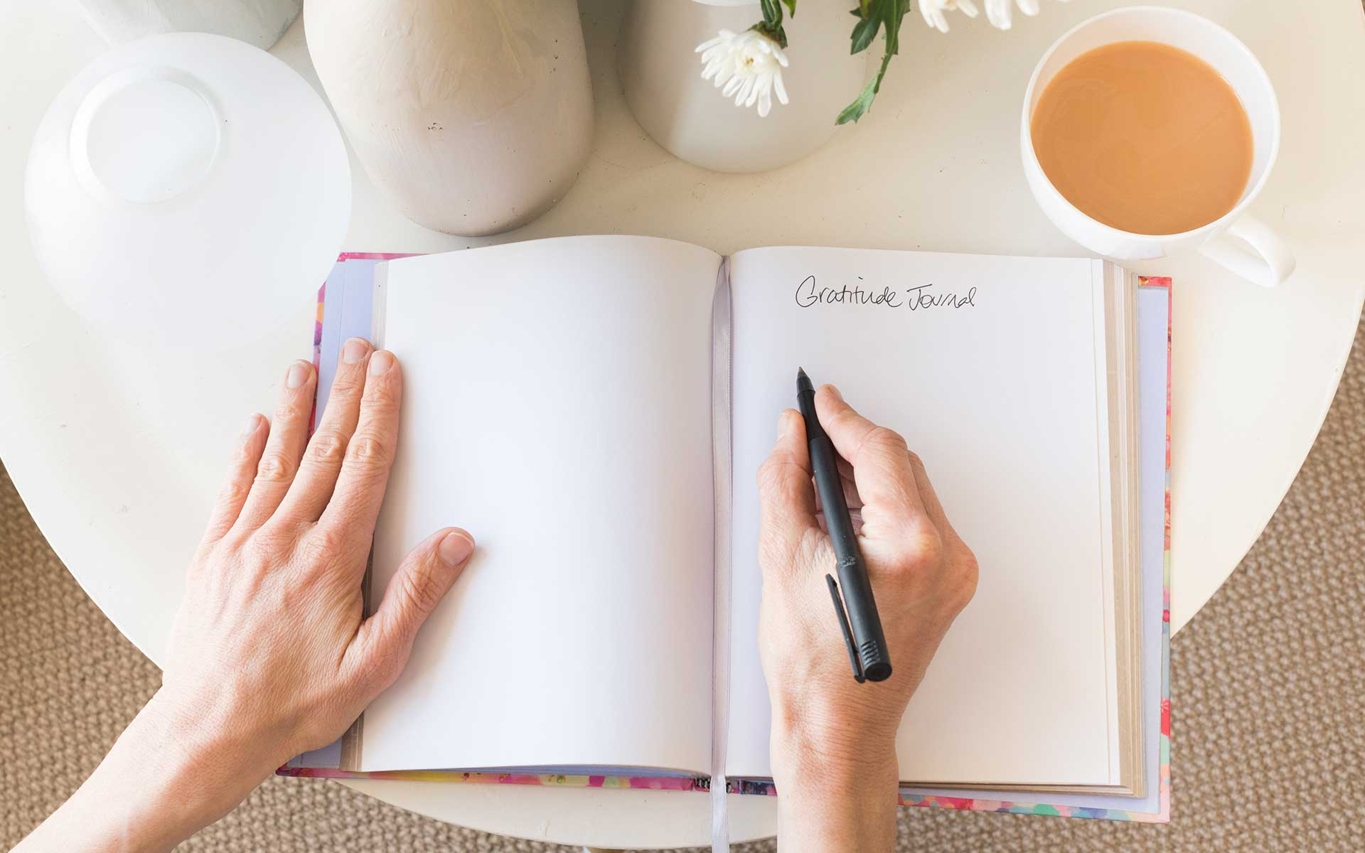 High angle cropped view of woman's hands writing in gratitude journal at desk with tea and flowers.