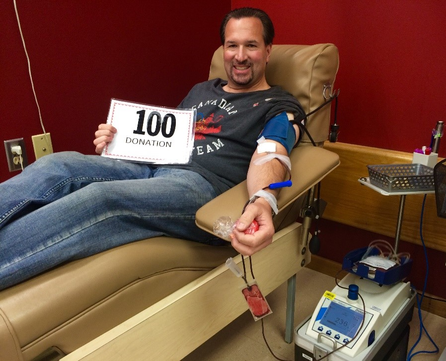 "Brian Geislinger donating blood holding ""100 donations"" card"