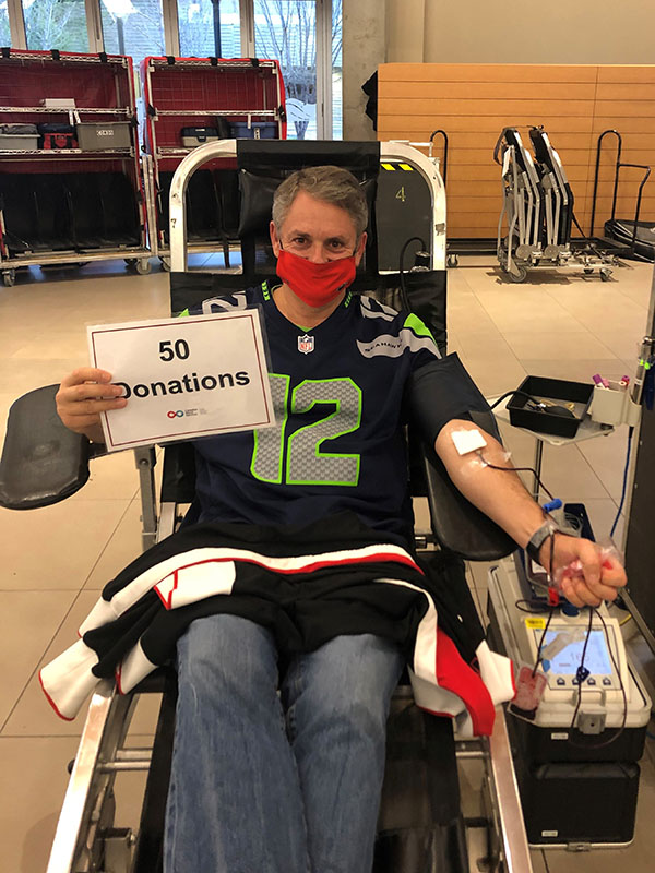 Kurt George holding up a sign that says 50 donations