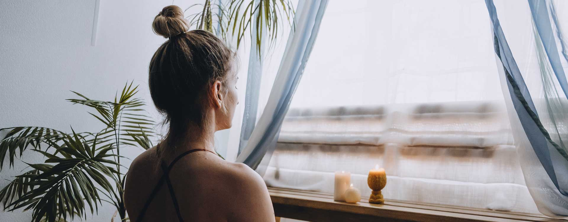 Woman meditating on the floor in front of a window with natural light and candles.