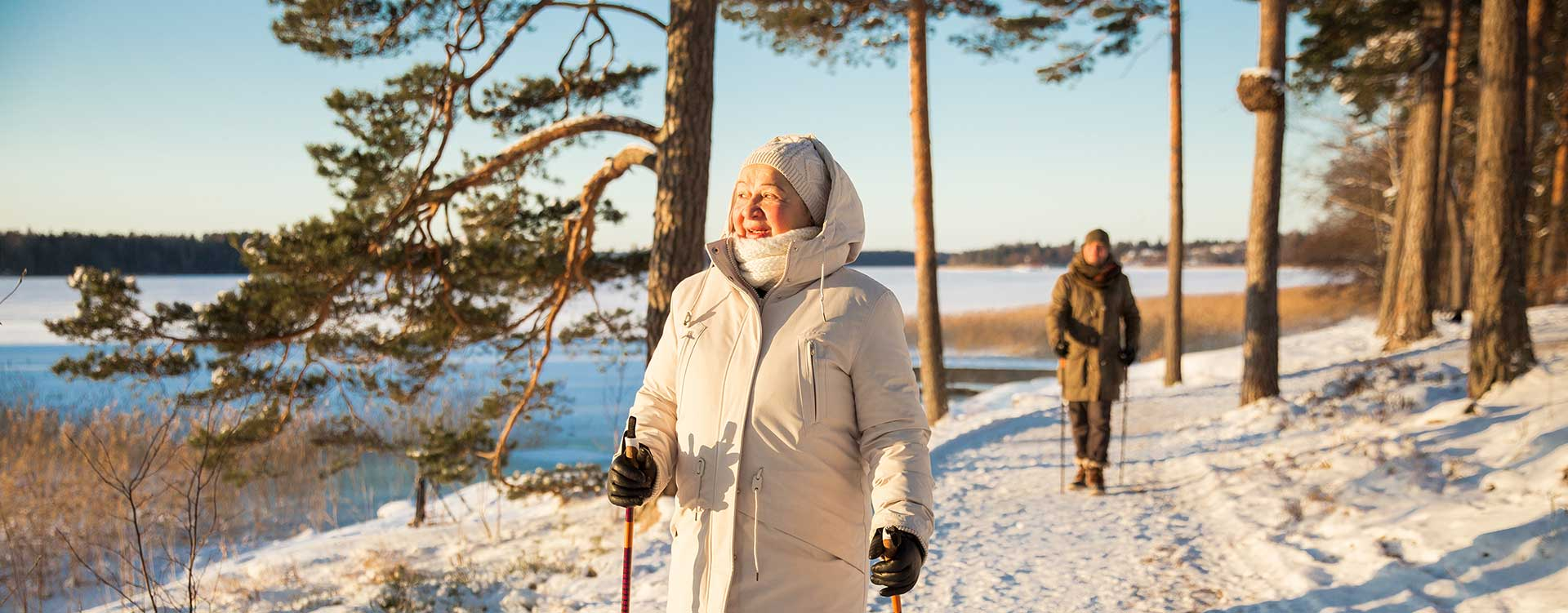 Senior woman and man hiking in winter forest during daytime.