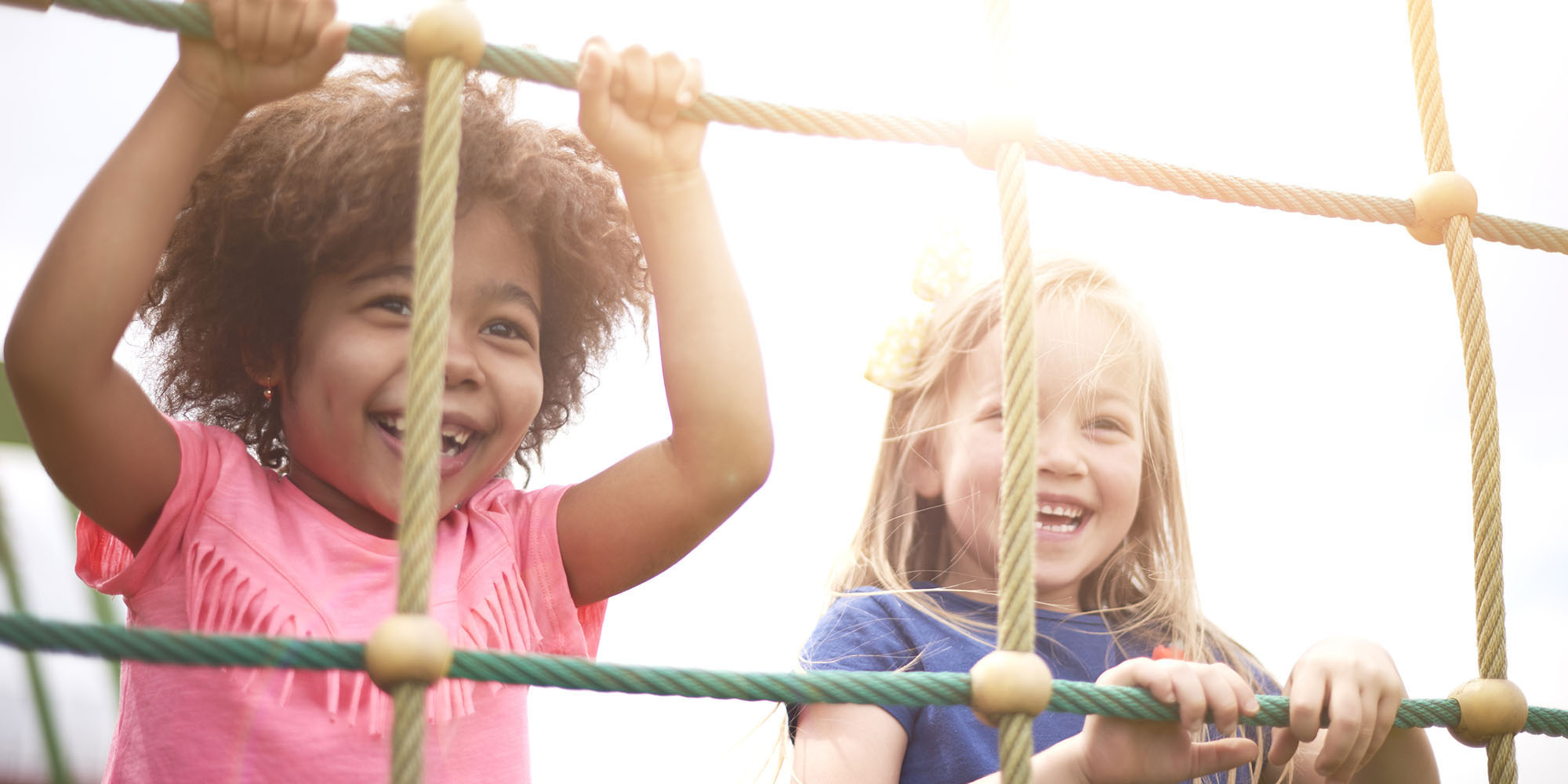 Two little girls playing together on a piece of playground equipment in the sun.