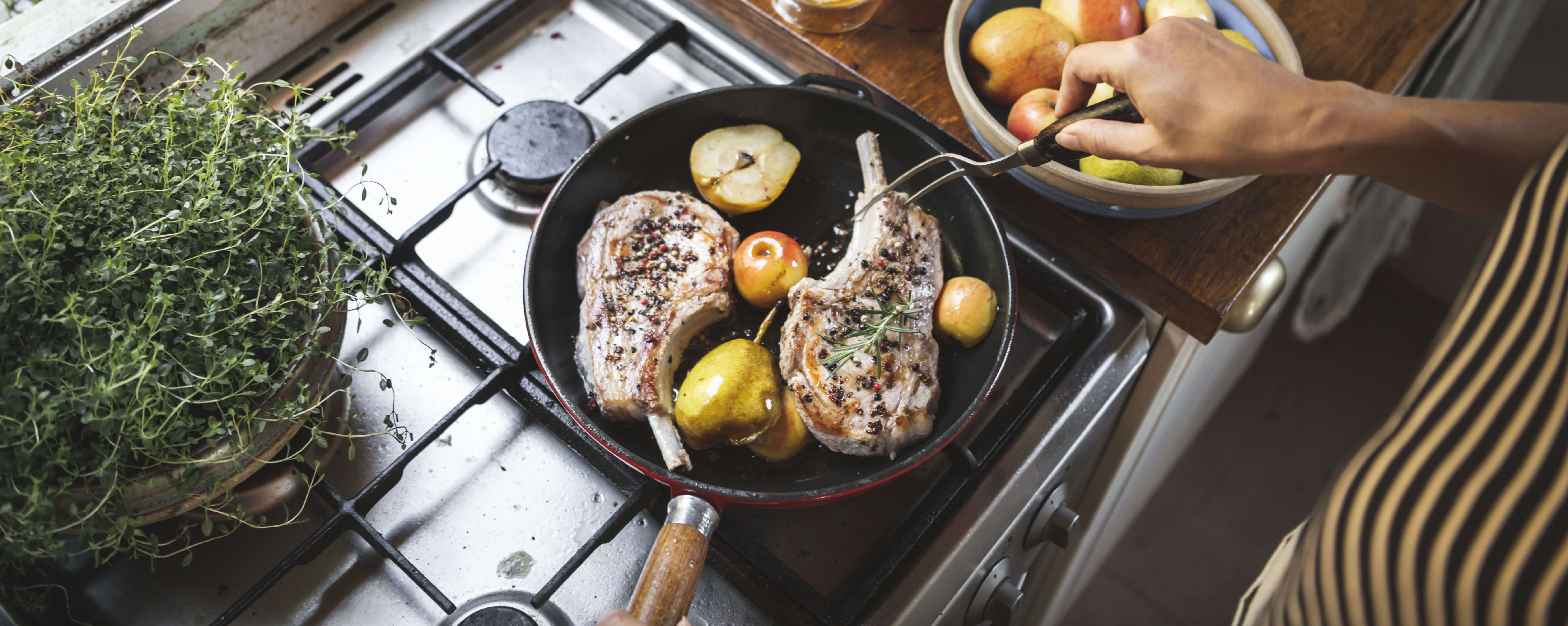 A person is cooking pork chops on a propane stovetop. In the frying pan are fresh herbs, apple and pear halves.